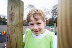 爬升套架的男孩在学校体育类 库存照片