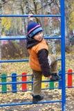 爬在操场的小男孩一架梯子 免版税库存图片