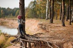 爬在步行的儿童女孩老杉树在河边 免版税图库摄影