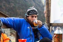爬山者喝茶在营地 库存图片