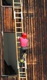 爬梯子的消防队员强悍头  库存图片