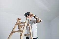 爬梯子的VR玻璃的年轻人 免版税库存照片
