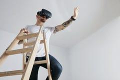 爬梯子的VR玻璃的年轻人 免版税库存图片