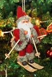 爬犁玩具的圣诞老人在圣诞树 图库摄影