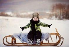 爬犁的小男孩在冬天 库存照片