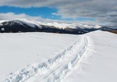爬犁踪影和脚印在冬天山小山冠上 免版税图库摄影