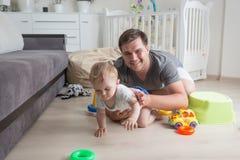 爬行与他的在地板上的男婴的愉快的父亲画象在 免版税图库摄影
