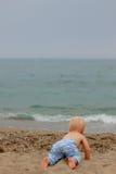 爬行到海的白肤金发的婴孩 免版税库存图片