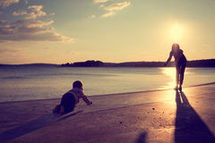 爬行到他的岸的母亲的小婴孩在海附近 图库摄影
