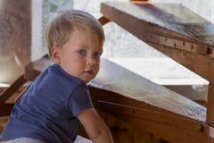 爬行台阶的男婴 看照相机的逗人喜爱的小孩 免版税库存图片