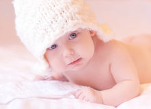爬行在与被编织的帽子的河床上的小婴孩  免版税库存图片