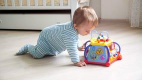 爬行在与音乐玩具的地板上的逗人喜爱的小孩男孩 库存图片