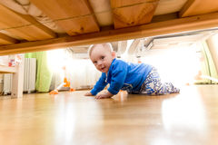 爬行在地板上和看在床下的男婴 免版税图库摄影