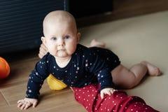 爬行在地板上和调查照相机的婴孩的画象 图库摄影