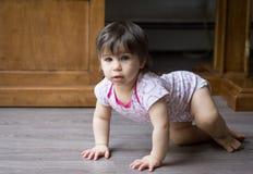 爬行在地板上的一个幼儿 免版税库存图片