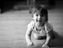 爬行在地板上的一个微笑的幼儿 免版税库存照片