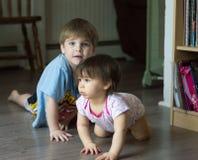 爬行在地板上的两个幼儿 库存照片