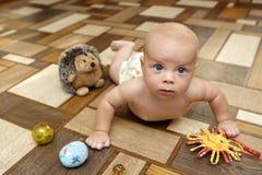 爬行在地板上的严肃的婴孩 库存图片