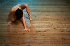 爬行在地板上的女孩在舞厅 免版税库存图片