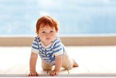 爬行在地板上的逗人喜爱的姜男婴 免版税库存照片