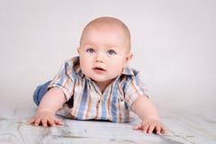 爬行在地板上的逗人喜爱的矮小的男婴 免版税库存图片