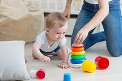 爬行在地板和聚集的玩具塔上的可爱的婴孩与mo 免版税库存图片