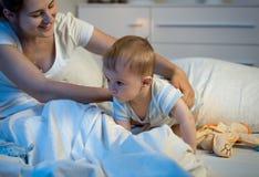 爬行在床上的逗人喜爱的男婴在晚上 图库摄影