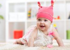 爬行在托儿所地板上的微笑的小孩子 免版税库存图片