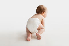 爬行在白色地板上的尿布的小婴孩 免版税库存照片