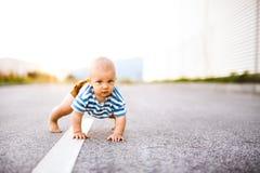 爬行外面在路的小男婴 免版税库存图片