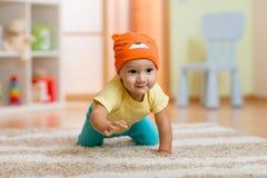 爬行的男婴在家在地板上 免版税库存照片