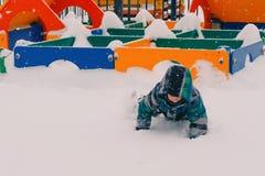 爬行通过在操场的随风飘飞的雪的男孩 免版税库存照片