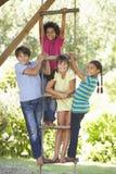 爬绳梯的小组孩子对树上小屋 库存图片