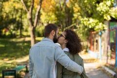 爱、关系、家庭和人概念-亲吻在秋天的微笑的夫妇停放 图库摄影
