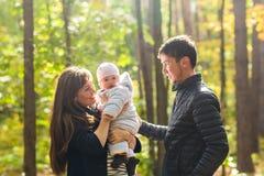爱、父母身分、家庭、季节和人概念-微笑的加上婴孩在秋天停放 免版税库存照片