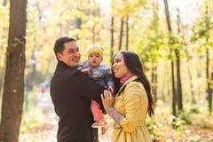 爱、父母身分、家庭、季节和人概念-微笑的加上婴孩在秋天停放 库存图片