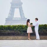 爱上束的夫妇在埃佛尔铁塔附近的白玫瑰在巴黎 免版税库存图片