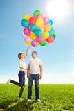 爱上气球的年轻夫妇在领域的手上反对 免版税库存图片