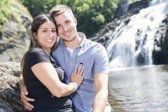 爱上瀑布的年轻夫妇在背景 库存照片