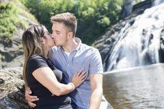 爱上瀑布的年轻夫妇在背景 免版税图库摄影