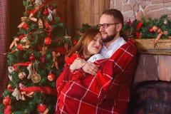 爱上红色格子花呢披肩的愉快的夫妇 免版税库存照片