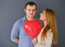 爱上红色气球心脏的美好的夫妇在情人节塑造,在灰色背景 免版税库存照片