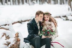 爱上花束的夫妇坐多雪的森林冬天婚礼的注册背景 附庸风雅 图库摄影