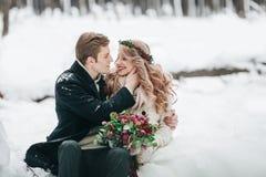 爱上花束的夫妇坐多雪的森林冬天婚礼的注册背景 附庸风雅 库存图片