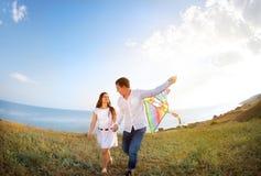 爱上飞行一只风筝的愉快的夫妇在海滩 图库摄影