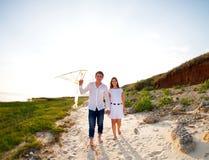 爱上飞行风筝的愉快的年轻夫妇 免版税库存图片