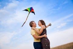爱上飞行风筝的年轻夫妇在乡下 免版税库存照片