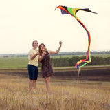 爱上飞行风筝的年轻夫妇在乡下 库存照片