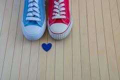 爱与两双不同运动鞋和蓝色心脏的背景 库存图片