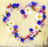 爱与心脏标志的概念由草甸花制成 免版税图库摄影